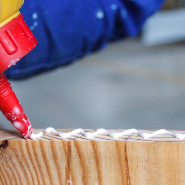 Carpenter at work using glue in his workshop