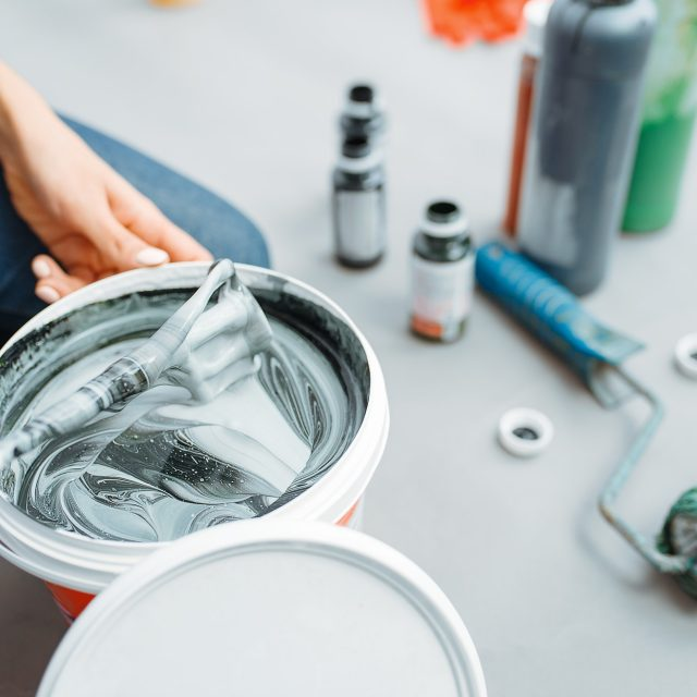 Female house painter mixes black and green paints